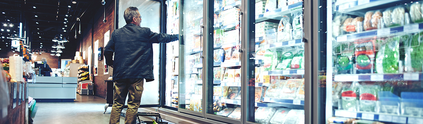 man reaching for food item in refrigerator in the refrigerated foods aisle at a grocery store